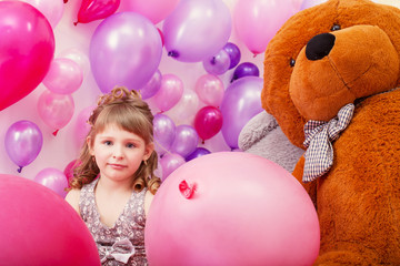 Beautiful curly girl posing among pink balloons