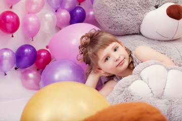Funny little girl posing lying on big plush bear