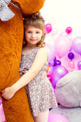 Happy little girl posing hugging big teddy bear