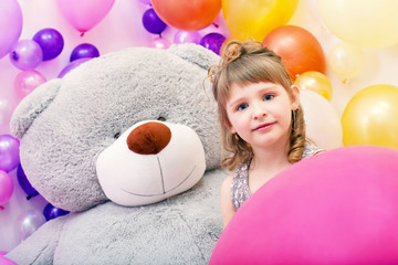 Portrait of blue-eyed girl with big teddy bear