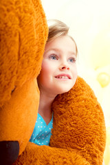Cute little girl in arms of teddy bear, close-up