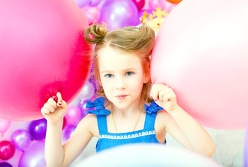 Funny little girl posing with colorful balloons