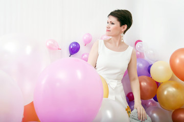 Elegant woman posing among colorful balloons