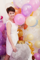 Charming woman posing with bunch of balloons