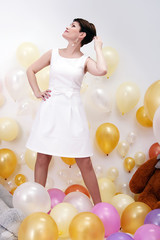 Stylish woman posing with balloons in studio