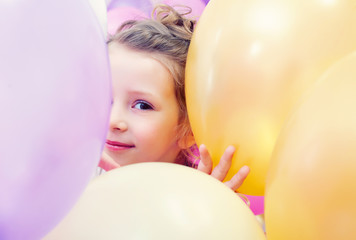 Cute little girl peeking out from behind balloons
