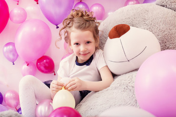 Smiling girl sits leaning on big teddy bear