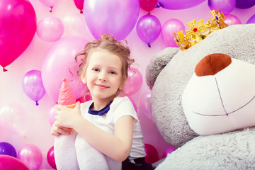 Smiling girl posing with ice cream in playroom