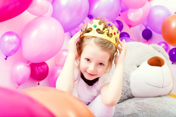 Portrait of funny little girl trying on crown