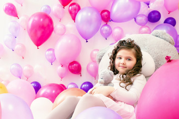 Playful little girl posing in studio with balloons