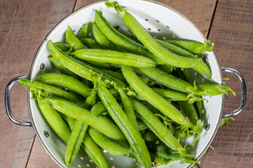 Fresh peas in a white colander