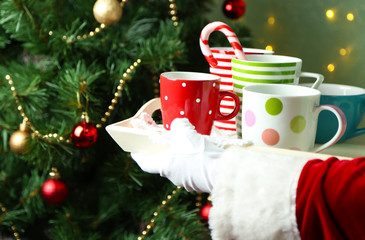 Santa holding  tray with mugs in his hand, on bright background