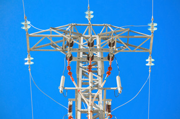 Detailed high voltage power line over brightly blue sky.