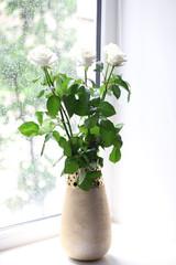 White roses in vase against window