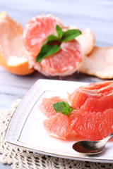 Ripe peeled grapefruits on plate, on color wooden background
