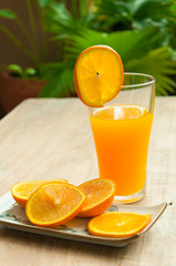 Glass of freshly pressed orange juice with sliced orange half on
