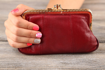 Female hand with stylish colorful nails holding little bag,