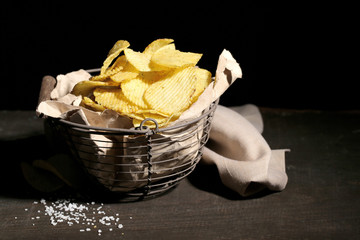 Tasty potato chips in metal basket