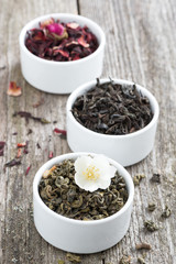 Assorted dry herbal teas in white bowls, vertical