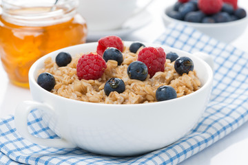 healthy breakfast - oat porridge with berries and honey