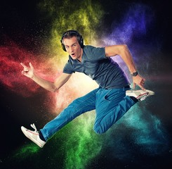 Man with headphones jumping against colourful powder explosion