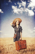 Brunette girl with suitcase on countryside.