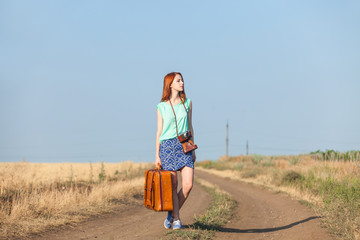 Redhead girl with suitcase on country road.