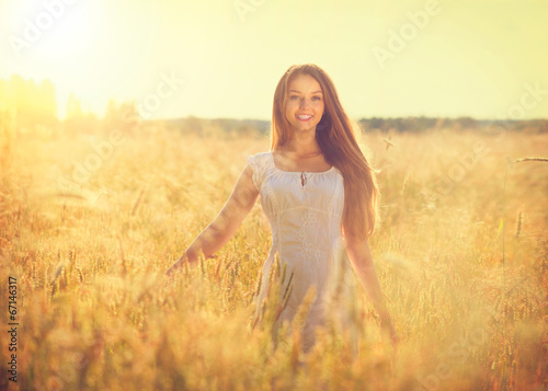 canvas print picture Beautiful teenage model girl in white dress running on the field