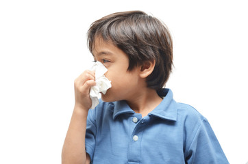 Sick little boy with tissue on white background