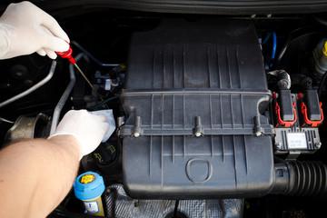 mechanic checks the oil level