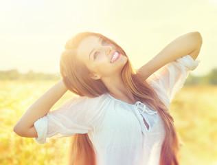 Beauty girl in white dress having fun on summer field