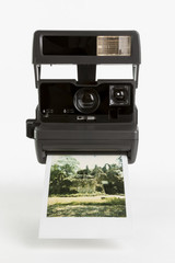 Old-fashioned instant camera with finished photoshot