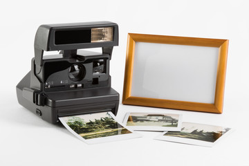 Old-fashioned instant camera, photoshots and blank photoframe