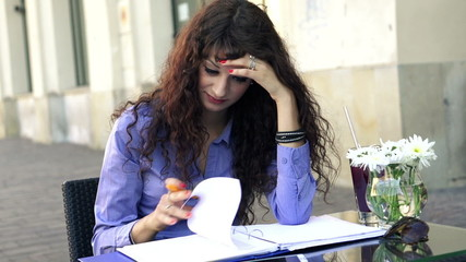 Overwhelmed, sad businesswoman with documents sit in cafe