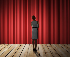 woman looking to red curtain