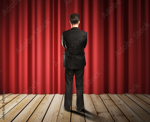 businessman looking to red curtains