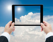 Businessman hands tablet taking pictures The sun and white cloud