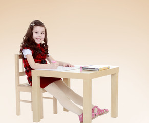 young girl sitting at the table.