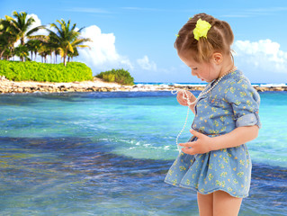little girl in a short blue dress on a sea background.
