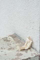 壁にもたれかかる人形