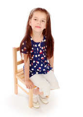 girl sitting on a small chair.