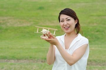 飛行機の模型を持っている女性
