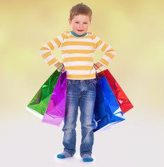 little boy in colorful bags goes to the store.