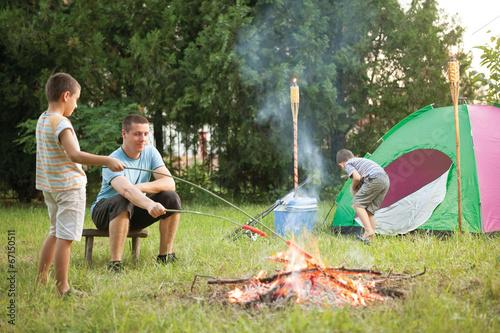 Fotobehang Kamperen happy family near campfire roasting sausages