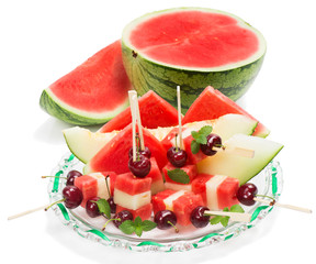 Salad with cut fruits on skewers, decorated with mint, on  glass