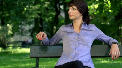 Attractive businesswoman relaxing, sitting on bench in park