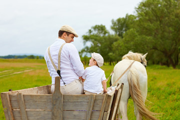 father and son, farmers ride a horse cart