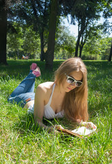 Girl in sunglasses reading a book in a summer park