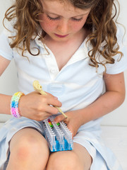 child  making a bracelet on a band loom