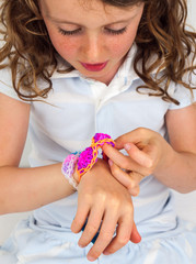 child  looking at a colourfull elastic bracelet